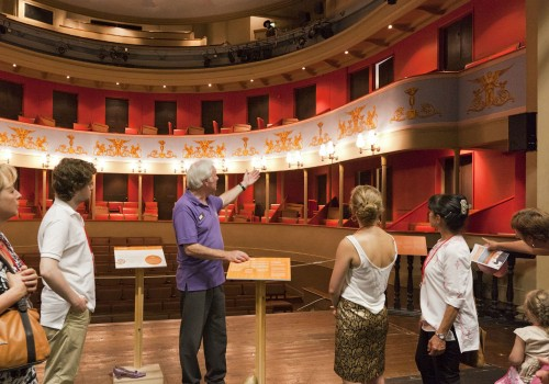 A tour guide on stage with a group looking out on to the auditorium