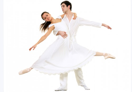 A male dancer holding a female dancer both all in white