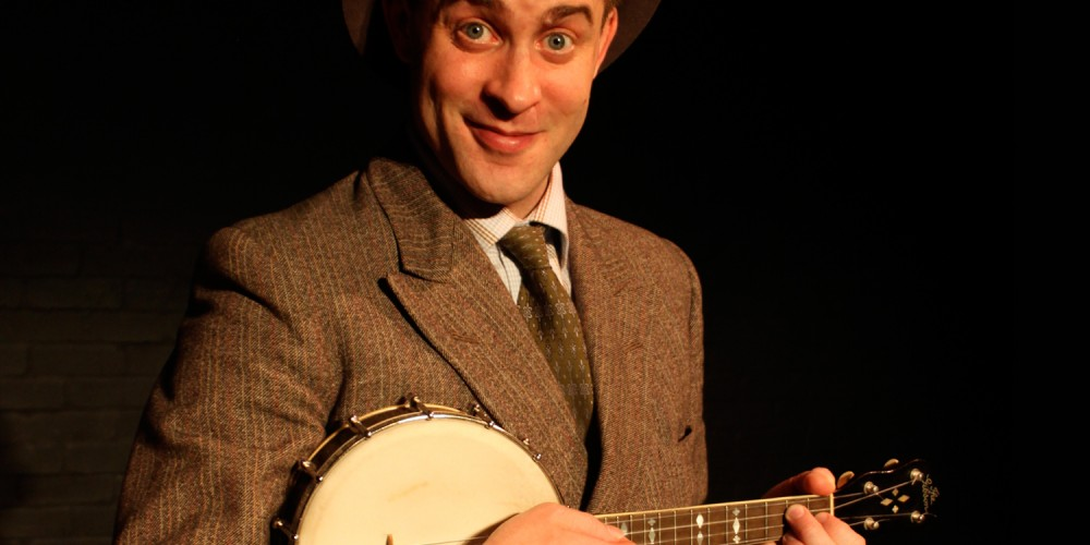 An actor wearing a suit and trilby hat playing a ukelele