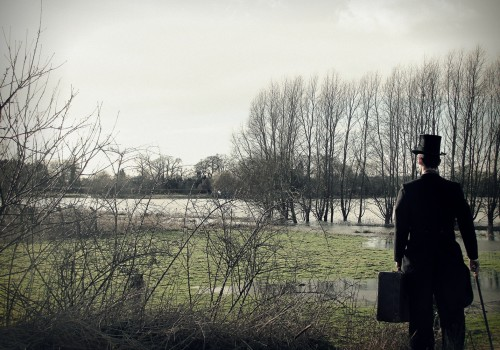 A man in a top hat with briefcase walking across a field