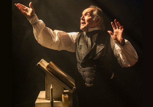 A man dressed in smart Victorian clothes stood at a pulpit with his arms reached out as a light shines upon his face