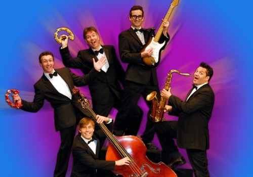 A group of musicians in suits holding their instruments; tambourines, guitars, Cello's and Saxophones, on a blue background