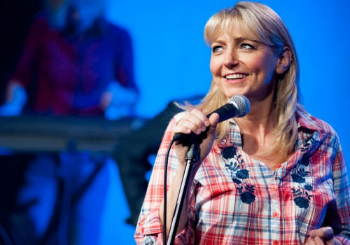 A blue background with a lady in a check shirt holding a microphone smiling