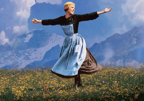 A young lady wearing an apron has her arms outstretched as she walks across a field with grass and yellow flowers on a mountain