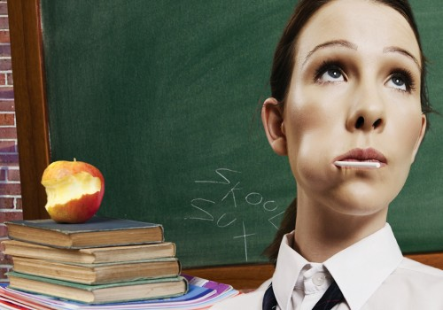 A school girls face with a lolly in her mouth looking upwards stood in front of a green chalk board and a pile of old books and a half eaten apple