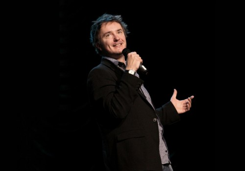 Dylan Moran standing with a microphone in his hand smiling, with his other hand stretched out against a black background